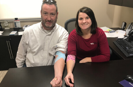 Two employees showing their arms with a bandage after donating blood for the nebraska community blood bank