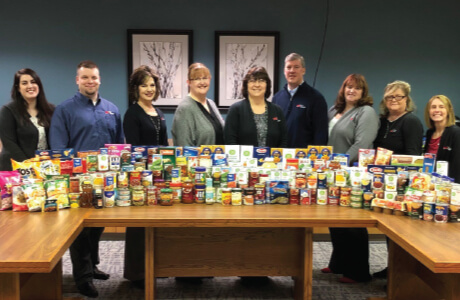 Group of Employees standing behind stacks of pantry items to be donated