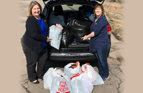 Two employees standing behind a car filled with bags of clothes to be donated