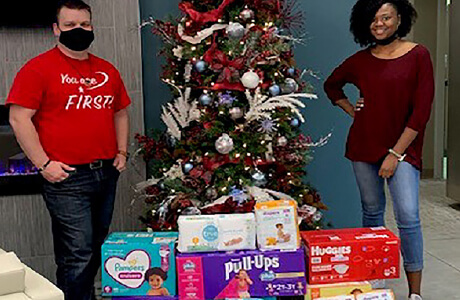 A group of employees standing behind boxes of diapers to be donated to the lydia house