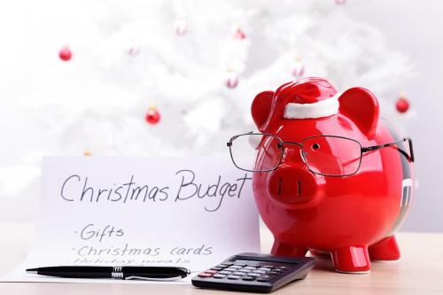 Piggy bank wearing glasses and santa hat looking at budget