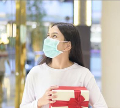 woman doing holiday shopping in a mask