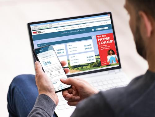 man using computer and phone to log into online and mobile banking